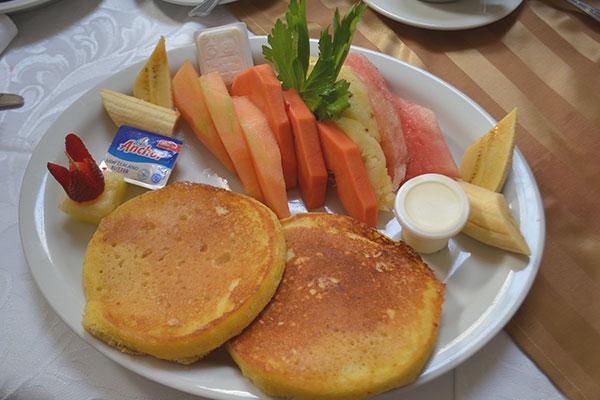 Deliciosos panqueques acompañados de maple y frutas.